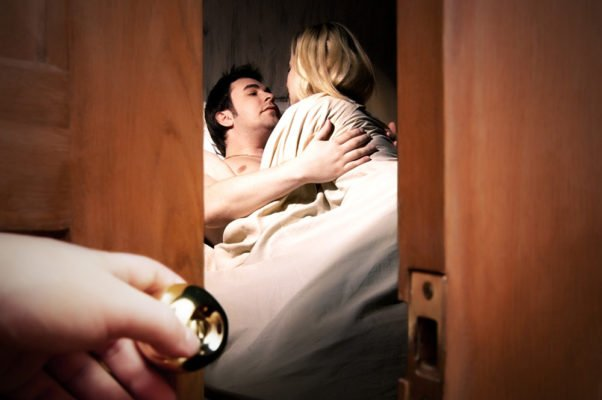 Couple caught in bed having affair